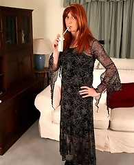 Lucimay is wearing a long dress and smoking seductively